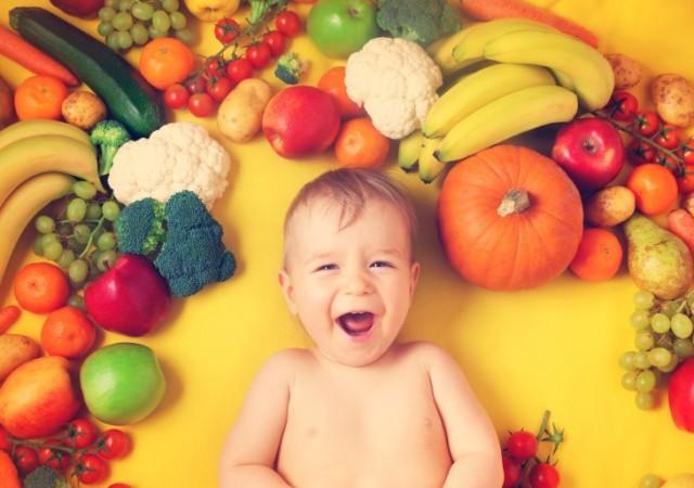 BabyWithVeggiesOnBrightBack.w730.web