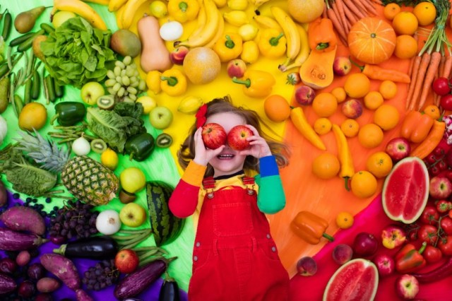 Child With Apple Over Eyes and Fresh Food Background