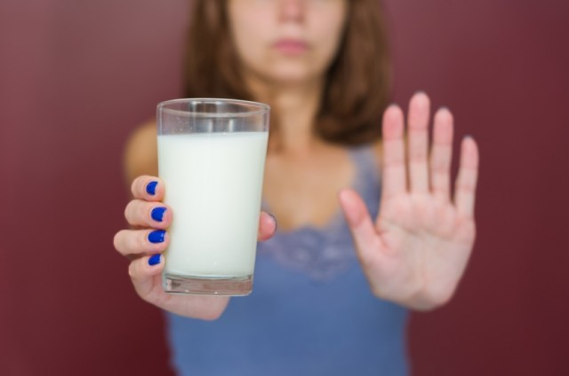 Woman with Milk Glass Holding Hand to Stop